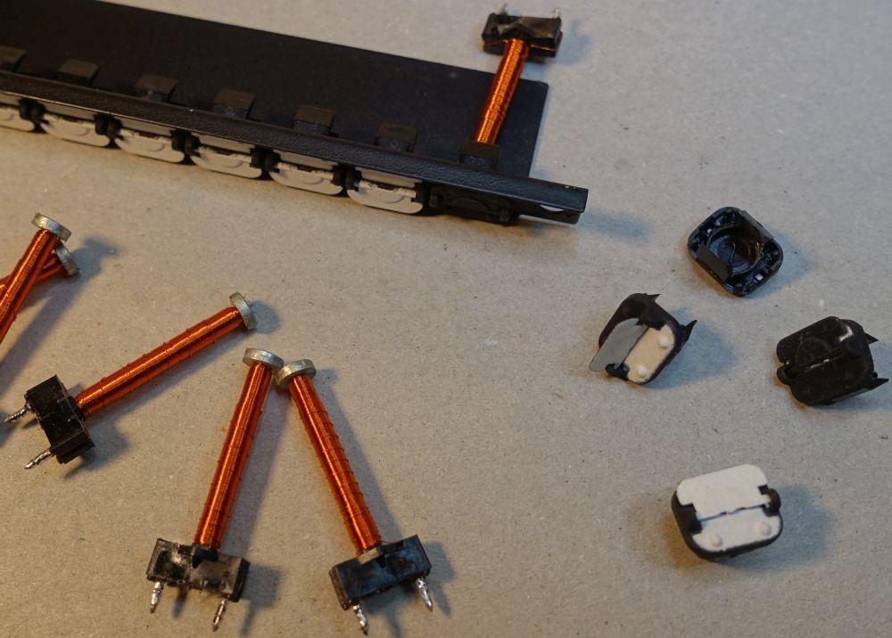 Einzelteile der Krüger Flip-Dot Module:<br>Dot-Grundkörper, magnetische Platte, Spule und Spaltenblech